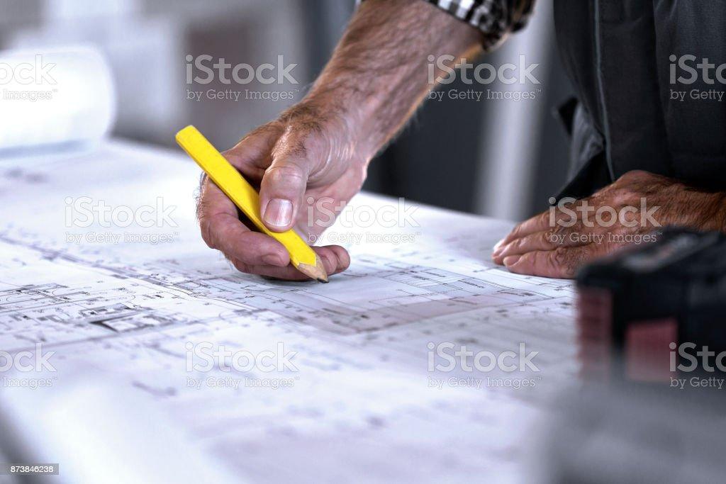 Carpenter making changes on blueprint stock photo