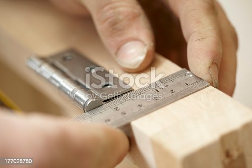 Carpenter in workshop workshop marking out wood to fit a hinge on a newly made cupboard. He is using a metal ruler and pencil and shot with a shallow depth of field.