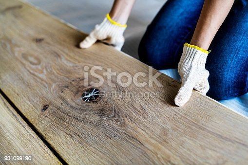 istock Carpenter man installing wooden floor 931099190
