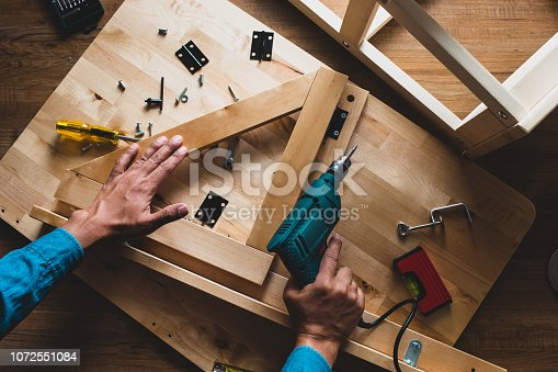530997702istockphoto Carpenter man working  with drill and furniture,fixing or repairing house. 1072551084