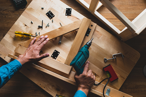 530997702 istock photo Carpenter man working  with drill and furniture,fixing or repairing house. 1072551084