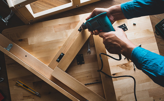 530997702 istock photo Carpenter man working with drill and furniture,fixing or repairing house.modern living concepts 1132215019
