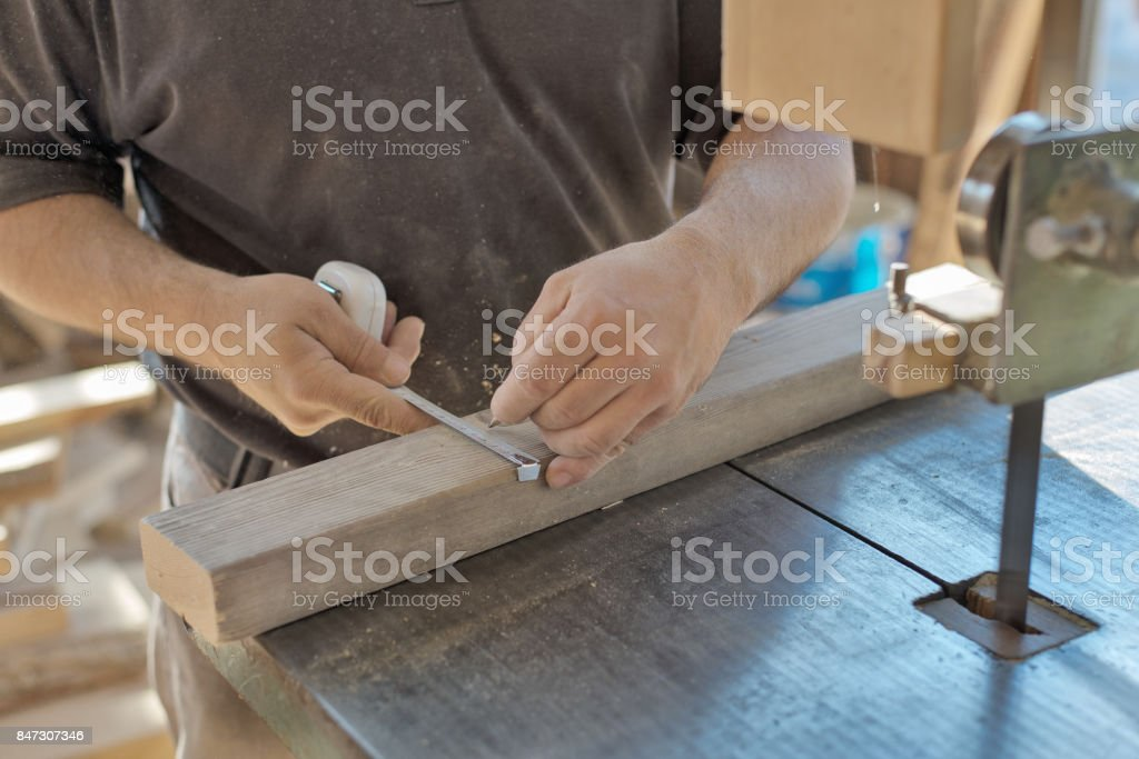 Carpenter marks the size with measuring tape and pencil. stock photo
