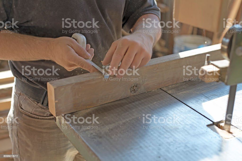 Carpenter marks the size with measuring tape. stock photo