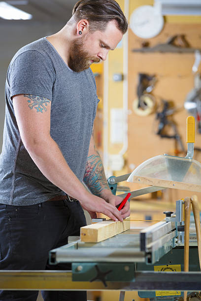 carpenter measure the length of a wood plank before sawing - baroque tattoo stock-fotos und bilder
