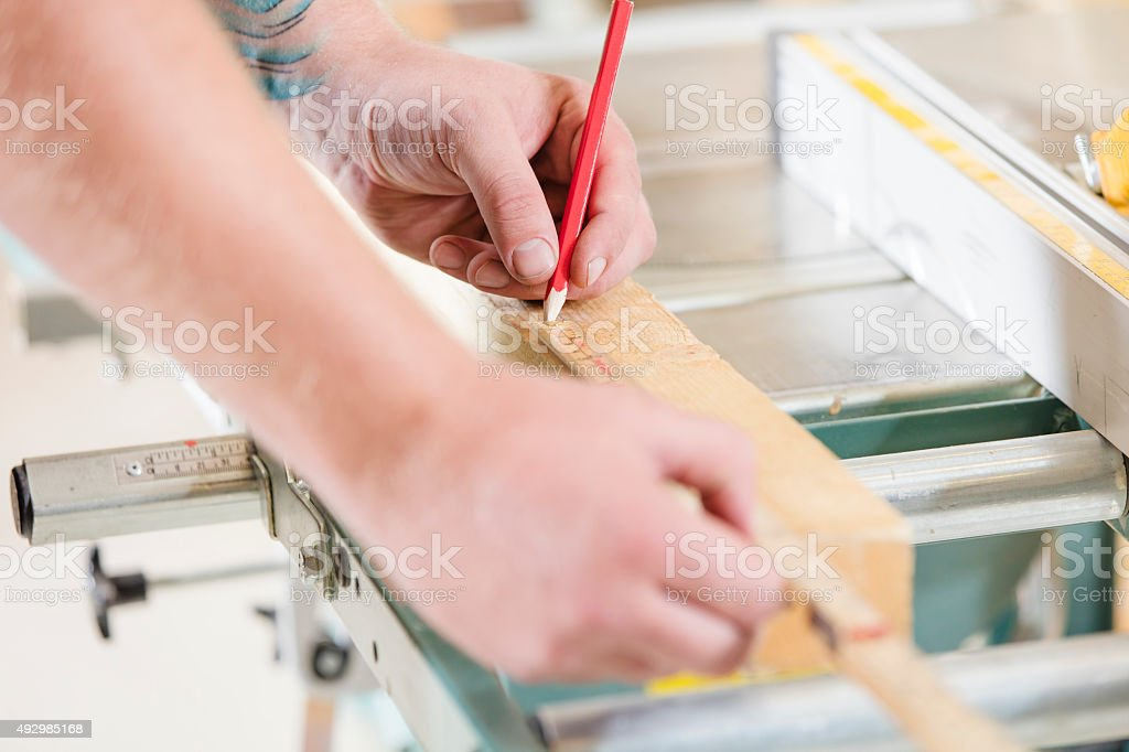 Carpenter measures the length of a wood plank before sawing stock photo