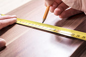 Carpenter Measuring A Wooden Board And Making A Mark With A Pencil