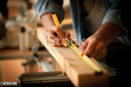 Closeup cropped view of a carpenter marking a measurement on a wooden plank. Horizontal shot.