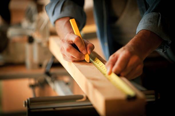 carpenter messen einem holz plank - schreiner stock-fotos und bilder