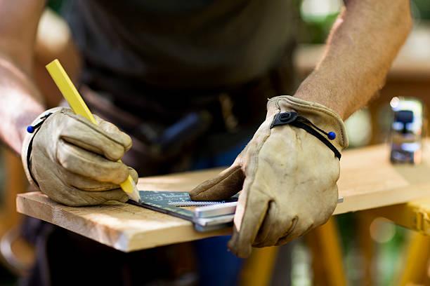 carpenter messen aus holz plank. - arbeitshandschuhe stock-fotos und bilder