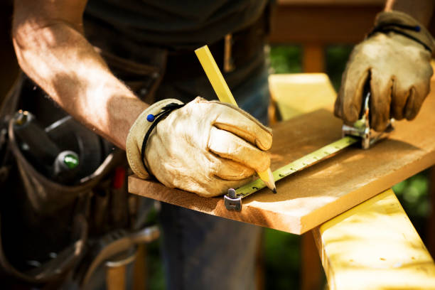 Carpenter Measuring A Wooden Plank. stock photo