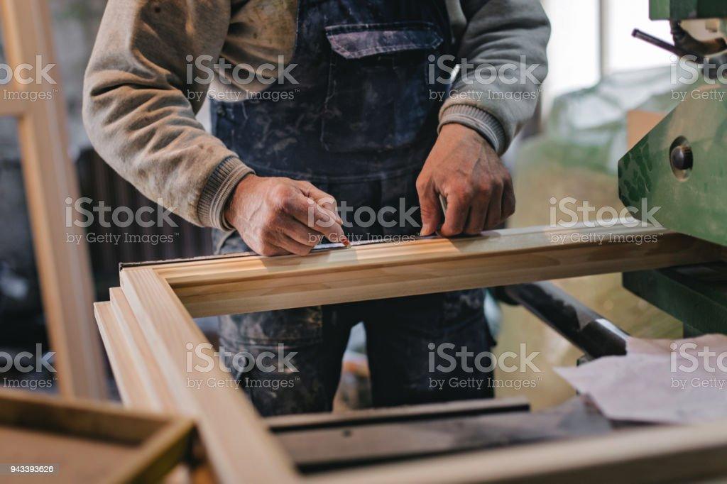 Carpenter Measuring a Wooden Plank stock photo