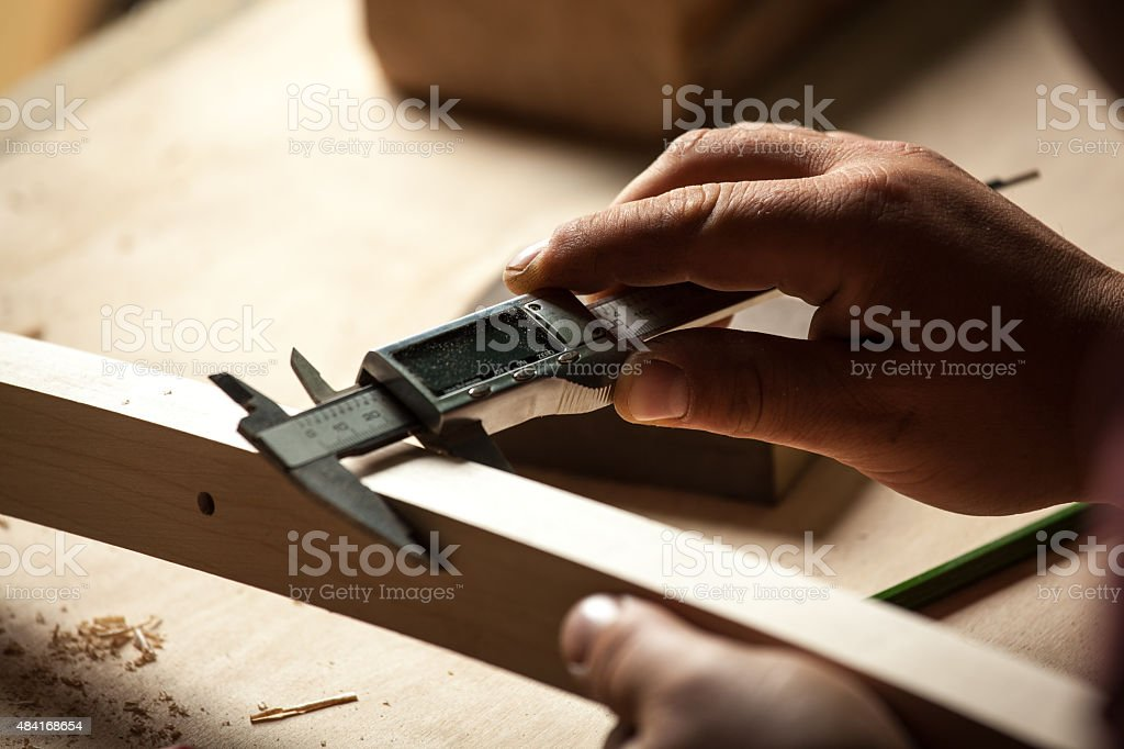 Carpenter measuring chair part with electric callipers. royalty-free stock photo
