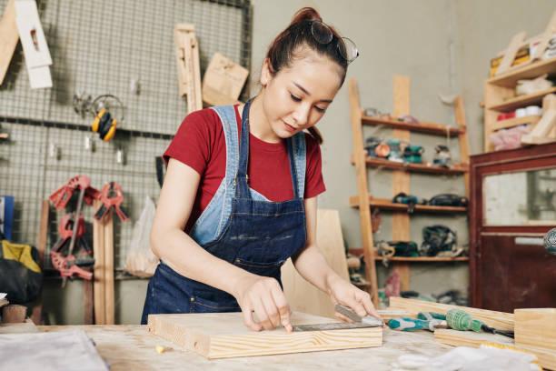 Carpenter measuring wooden board stock photo