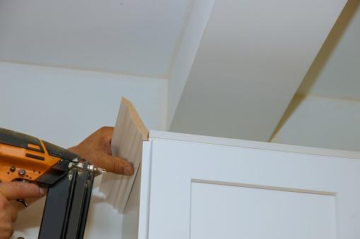 istock Carpenter nailing crown moldings in the kitchen cabinets framing trim worker using brad nail gun 1191804016