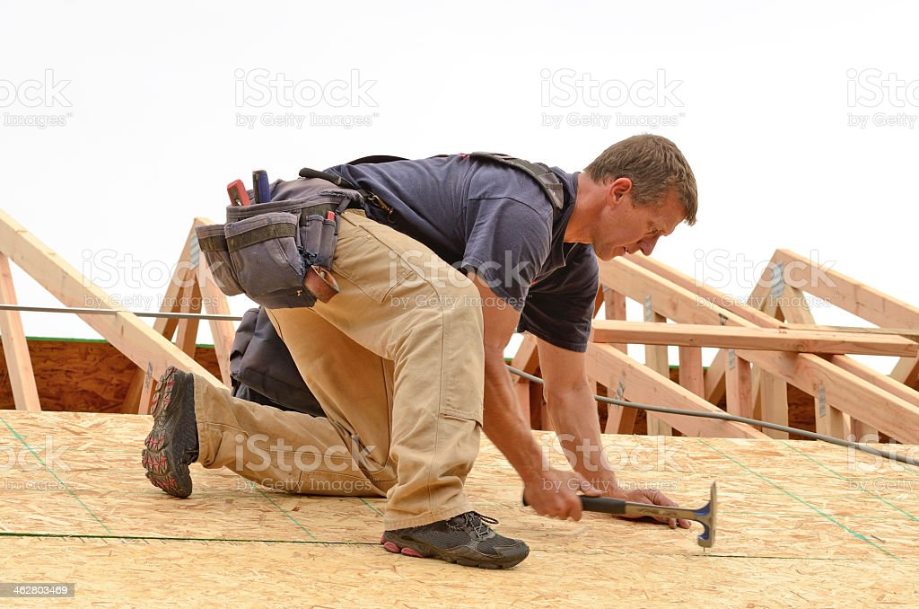 Carpenter nailing down roof boards stock photo
