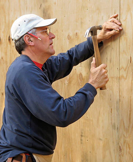 Carpenter nailing plywood stock photo
