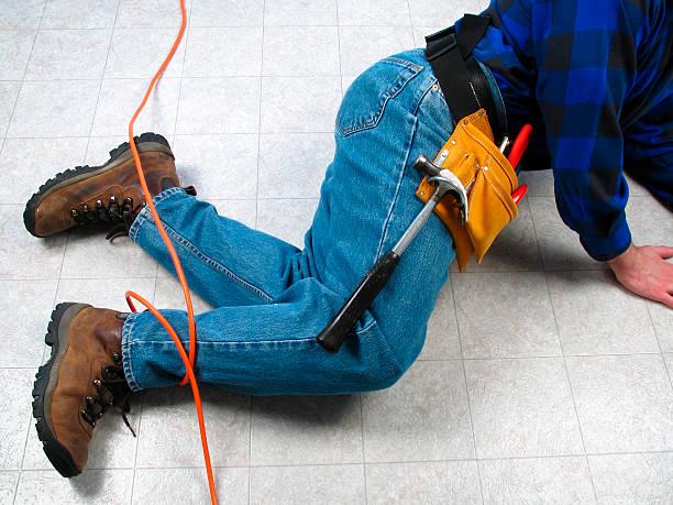 carpenter oder bauarbeiter stolpern auf orange verlängerungskabel - kabelschuhe stock-fotos und bilder