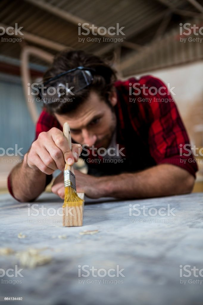 Carpenter painting a piece of wood foto stock royalty-free