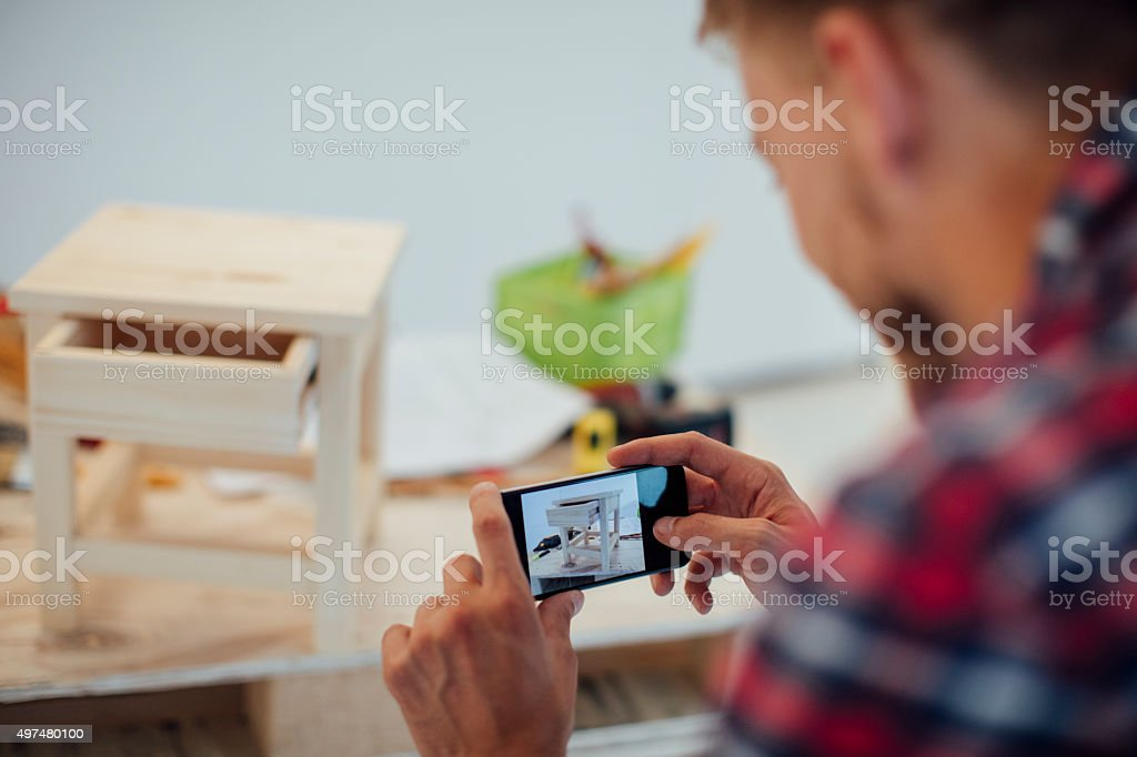 Carpenter Photographing Furniture With His Phone. stock photo