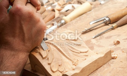 A carpenter is carving a piece of furniture