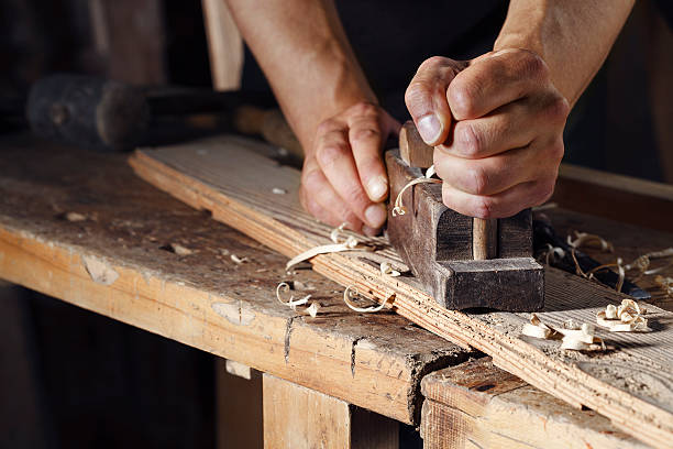 carpenter planing a plank of wood with a hand plane Close up of a carpenter planing a plank of wood with a hand plane carving craft activity stock pictures, royalty-free photos & images