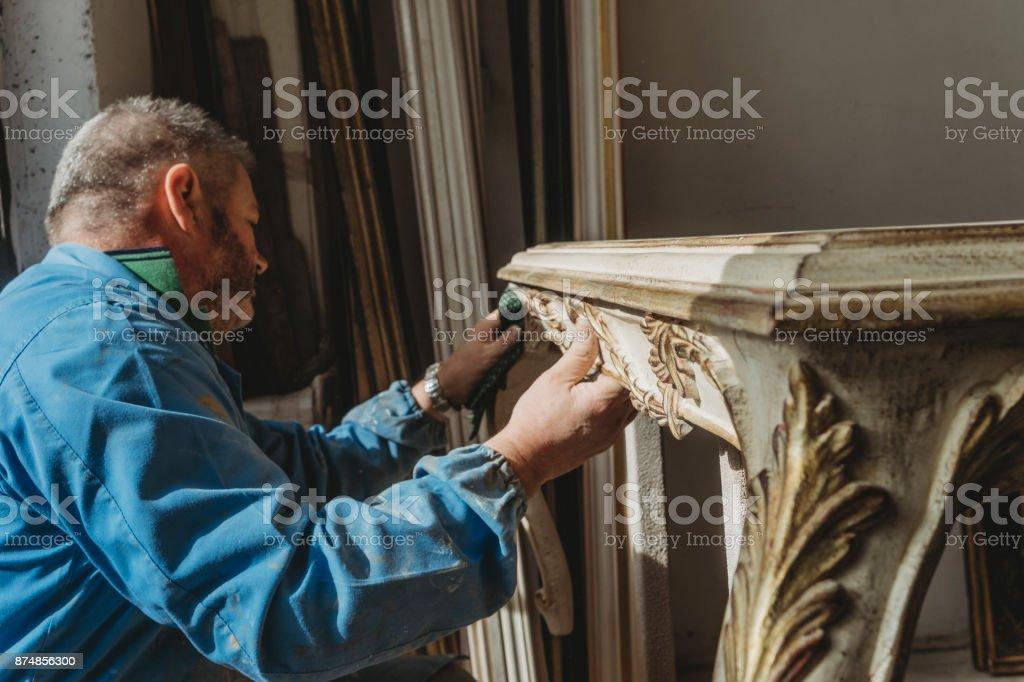 Tischler Polieren einer wiederhergestellten Tabelle Lizenzfreies stock-foto