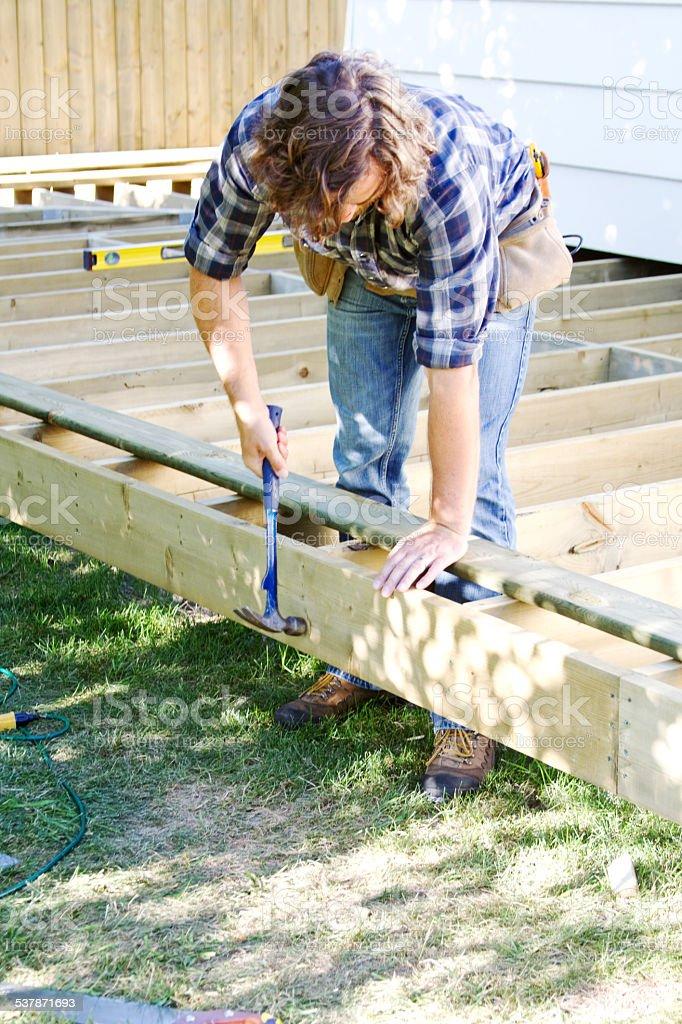 Carpenter pounding a nail stock photo