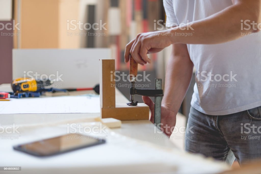 Carpenter puts the clamp on wood royalty-free stock photo