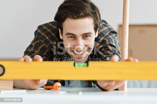 Carpenter, repairman, contractor, builder, handyman, blogger at work, favorite profession and home repair. Happy young handsome man measuring with ruler in living room interior, close up, copy space