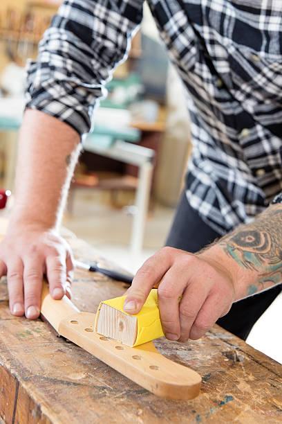 carpenter abgeschmirgelten eine gitarre ausschnitt in holz im workshop - baroque tattoo stock-fotos und bilder