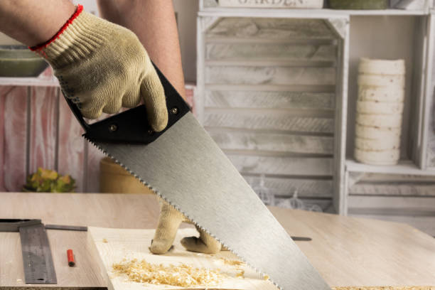 Carpenter sawing a board with a hand wood saw. stock photo