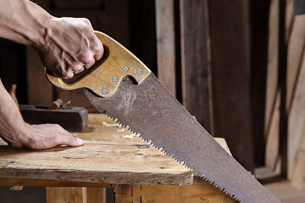 carpenter sawing a board with a hand wood saw - saw stockfoto's en -beelden