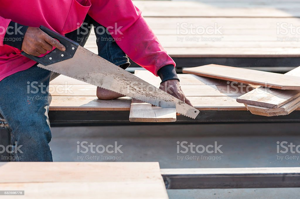 Carpenter sawing a board with a hand wood saw stock photo