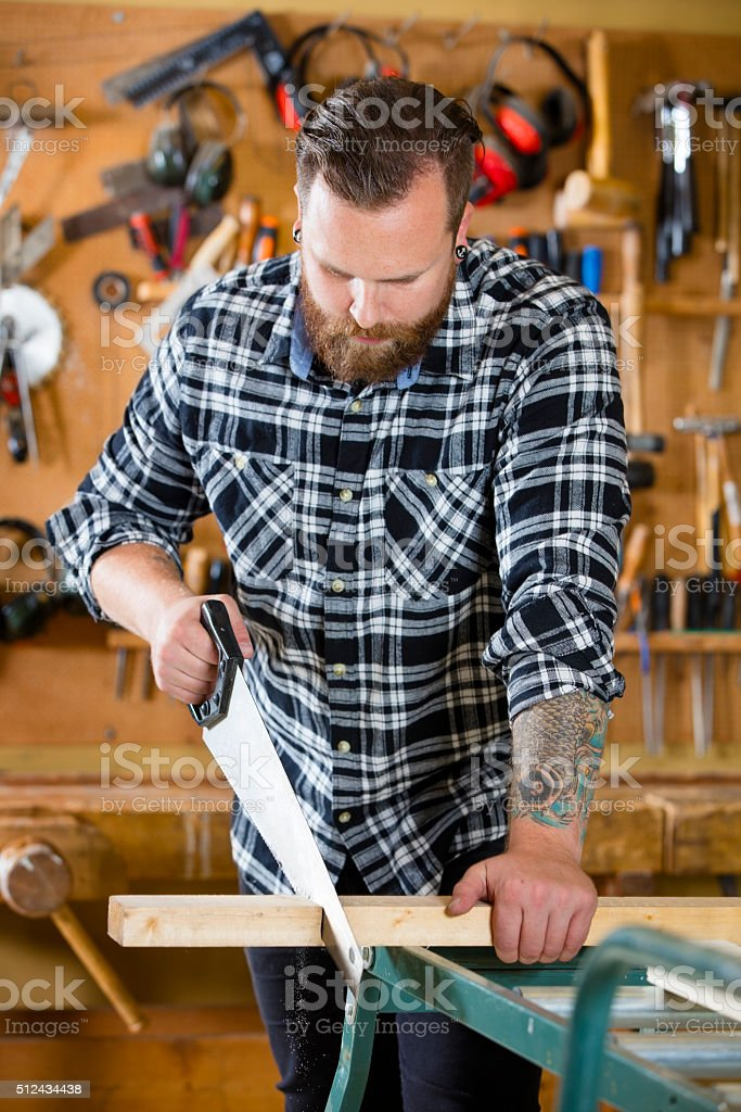 Carpenter sawing wood with hand saw in workshop stock photo