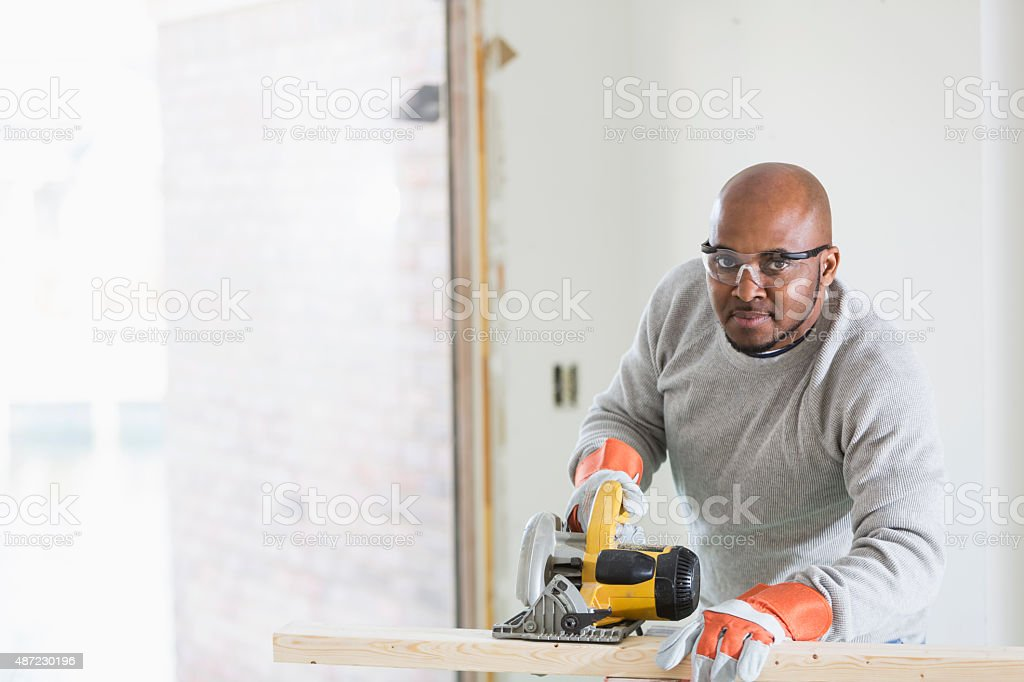 Carpenter sawing wood with power tool stock photo