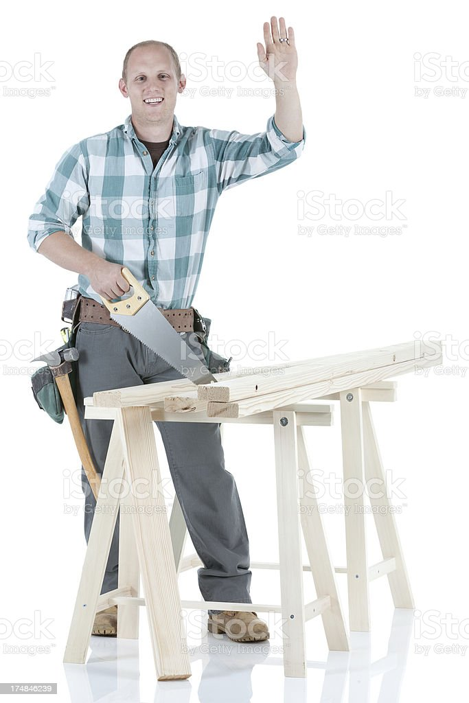 Carpenter sawing wooden planks and waving his hand stock photo