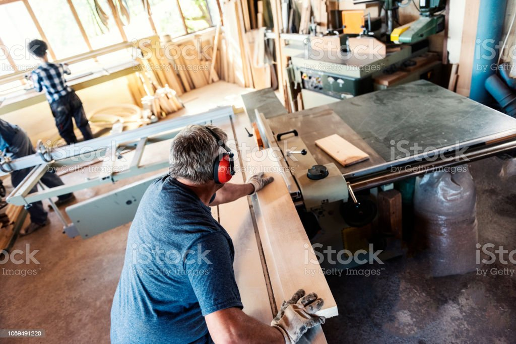 Carpenter sawing wooden planks Carpenter sawing wooden planks Active Seniors Stock Photo
