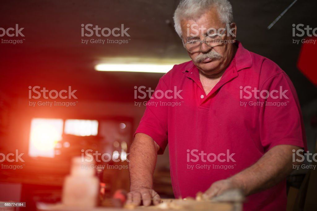 Carpenter scraping wood with antique planer royalty-free stock photo