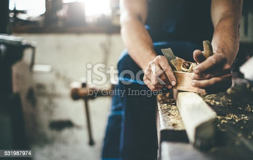 carpenter working with planer at the workshop. closeup view of carpenter's hands
