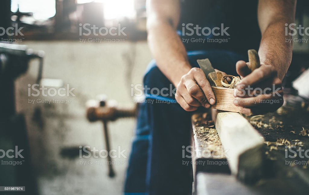 carpenter scraping wood with planer stock photo