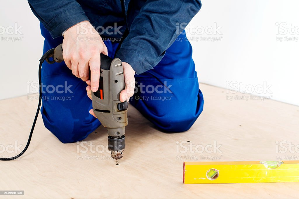 Carpenter screw screwdriver spin into a sheet of plywood stock photo