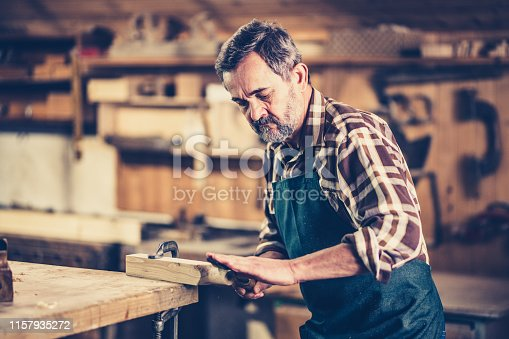Mature carpenter shaping wood with rasp in workshop.