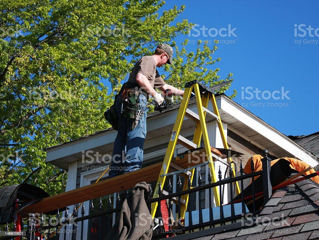 carpenter shingling roof stock photo