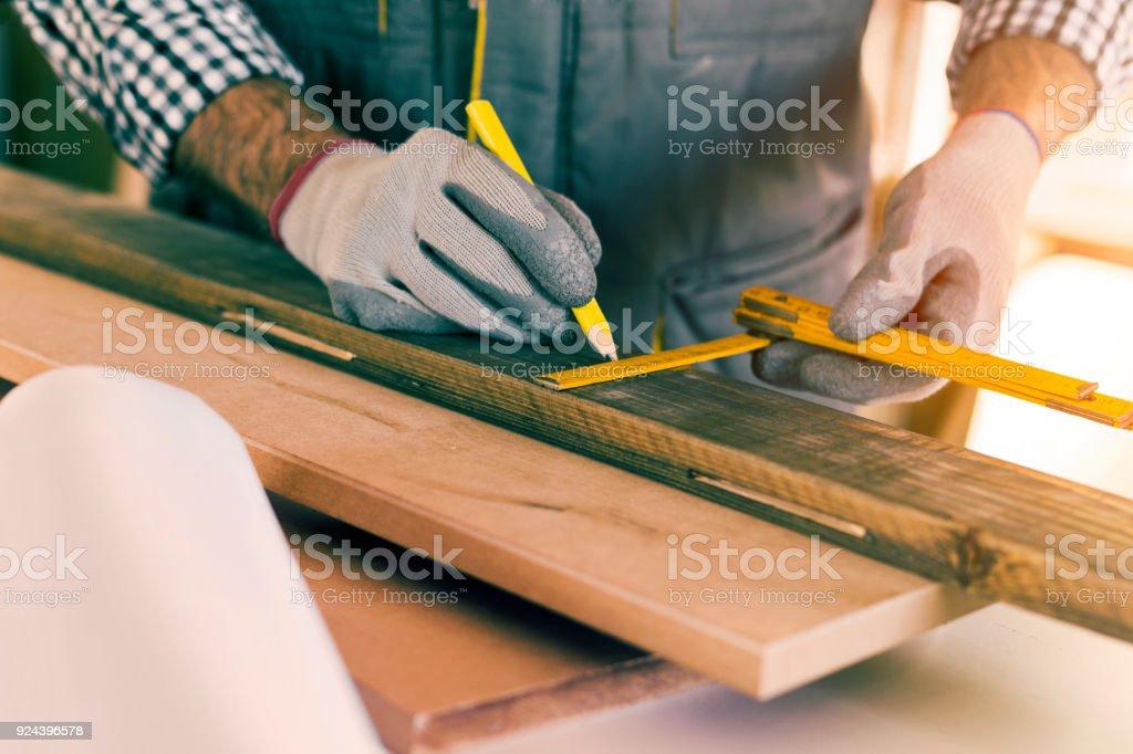 Carpenter taking measurement stock photo