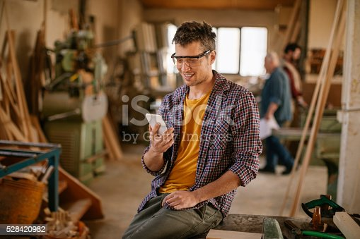 istock Carpenter texting while working 528420982