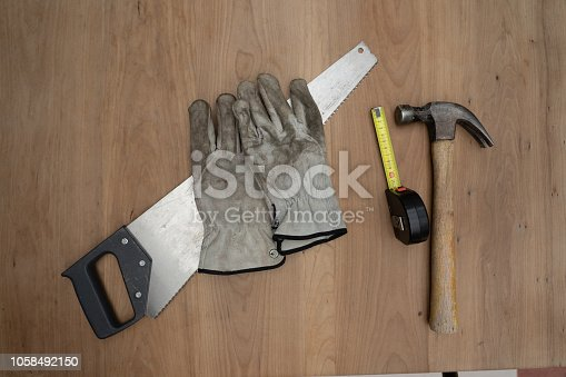Tools that can be used by a carpenter are displayed on a woorden taebel. These can be a hamer, measuring tape, protective gloves and a saw