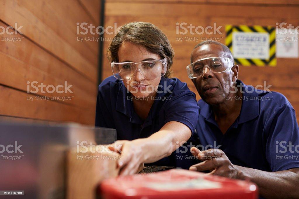 Carpenter Training Female Apprentice To Use Plane stock photo