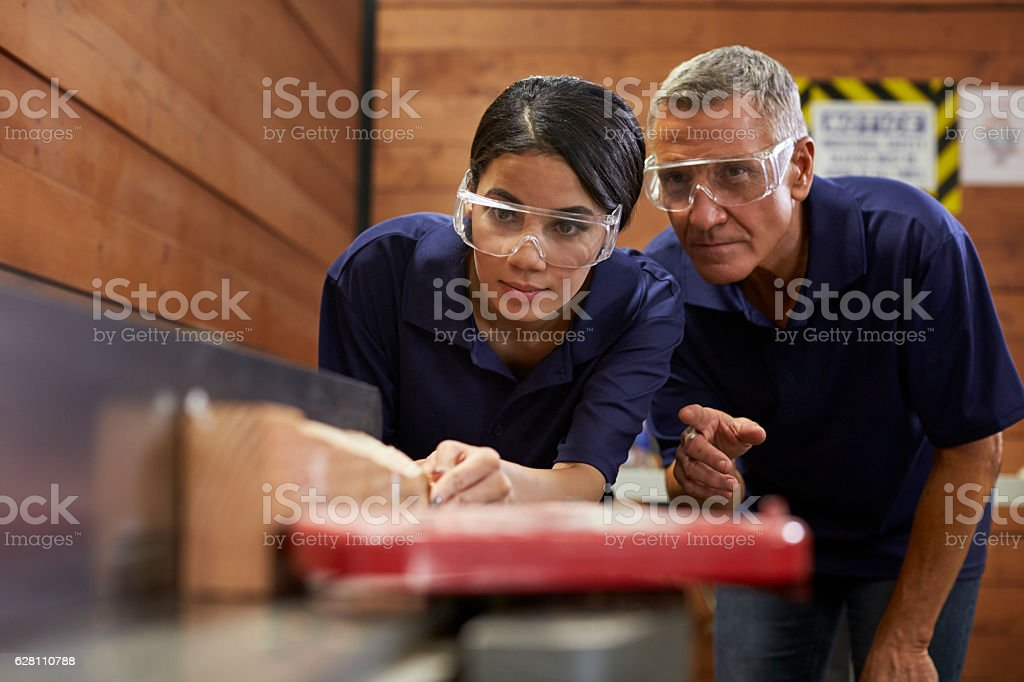 Carpenter Training Female Apprentice To Use Plane stock photo