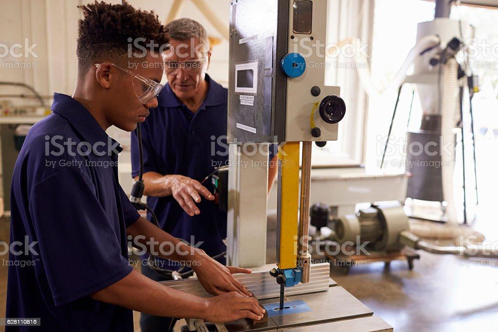 Carpenter Training Male Apprentice To Use Mechanized Saw stock photo